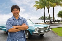 Asian man in front of car