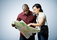 Multi-ethnic couple looking at map