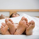 Multi-ethnic couple's bare feet on bed