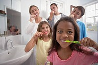 Multi-ethnic family brushing teeth