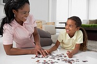 African American mother and daughter playing with puzzle