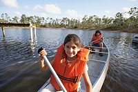 Hispanic sister and brother paddling in canoe