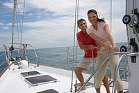 Multi-ethnic couple pulling rope on sailboat