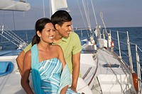 Multi-ethnic couple sitting on sailboat