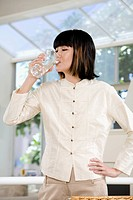 Asian woman drinking glass of water