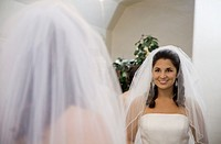 Hispanic bride looking in mirror