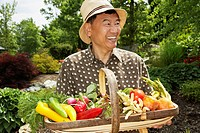 Senior Asian man holding basket of vegetables