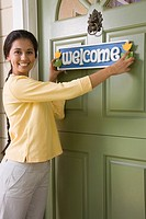 Mixed Race woman hanging Welcome sign
