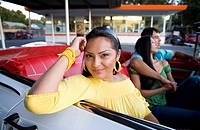 Hispanic woman with friends in convertible (thumbnail)