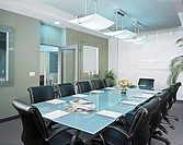 A meeting room with a glass table and black leather chairs