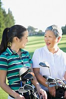 Asian mother and adult daughter holding golf bags