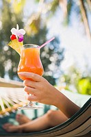 Asian woman with cocktail in hammock (thumbnail)