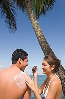 Asian woman applying sunscreen to boyfriend
