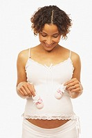 Pregnant Mixed Race woman holding baby shoes