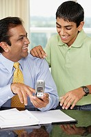 Middle Eastern father and son looking at cell phone