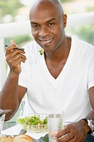 African American man eating salad