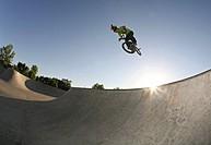 A man performing tricks with his BMX bike on a skate ramp