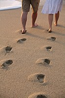 A man and woman leave footprints behind in the sand as they walk along a beach