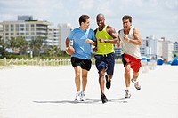 Multi-ethnic men running in beach