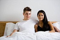 Multi-ethnic couple sitting in bed