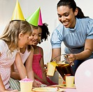 Mixed Race woman pouring drink at daughter's party