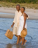 Senior African American couple walking in water