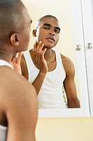 African man looking in mirror