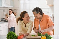 Hispanic woman and adult granddaughter chopping vegetables