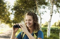 Smiling teenage girl with binoculars
