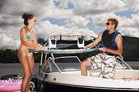 Teenage couple on boat with water ski