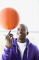 Smiling athlete spinning basketball on finger