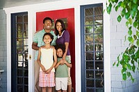 Smiling family at house door