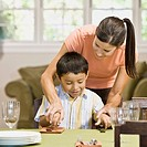 Hispanic mother showing son proper silverware placement