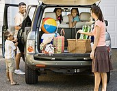 Hispanic family loading car for trip