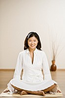 Asian woman sitting on meditation mat