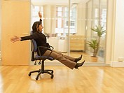 Indian businesswoman rolling in office chair