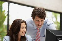 Businesspeople looking at a computer monitor