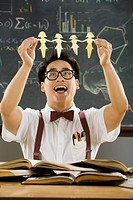 Nerdy Asian male student holding cut-out paper dolls