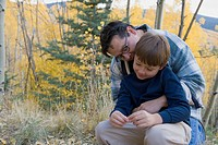 Hispanic father hugging son in woods