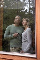 Couple looking out of window of cabin