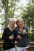 Women standing on deck drinking red wine