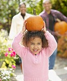 African girl holding pumpkin on head