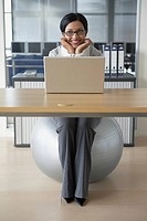 Businesswoman sitting on fitness ball (thumbnail)