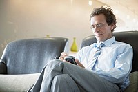 Businessman using personal digital assistant