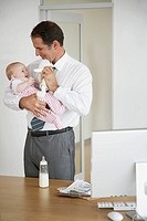 Businessman playing with his baby