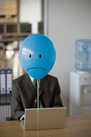 Businessmen with sad faced balloon