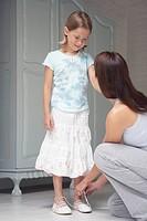 Mother tying daughter´s shoe