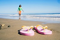 Flip-flops on beach in front of woman