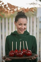 Woman carrying tray of candy apples