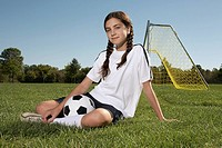 Girl sitting in soccer field